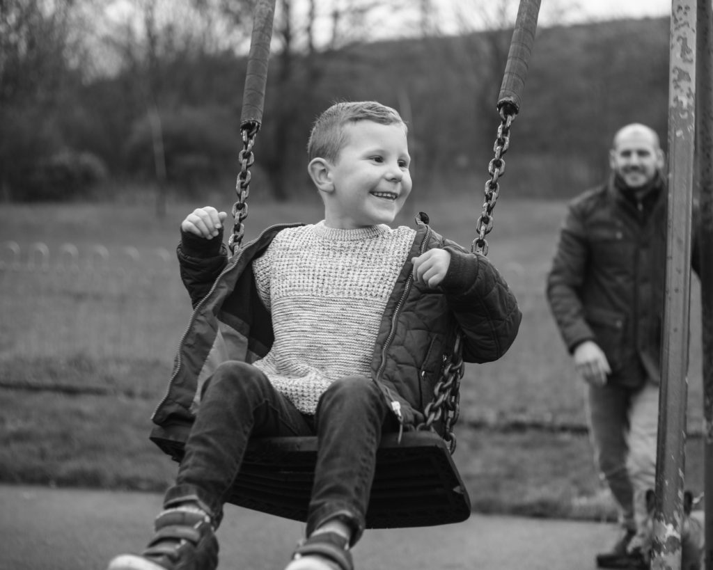 Dad pushing boy on a swing, documentary family photography