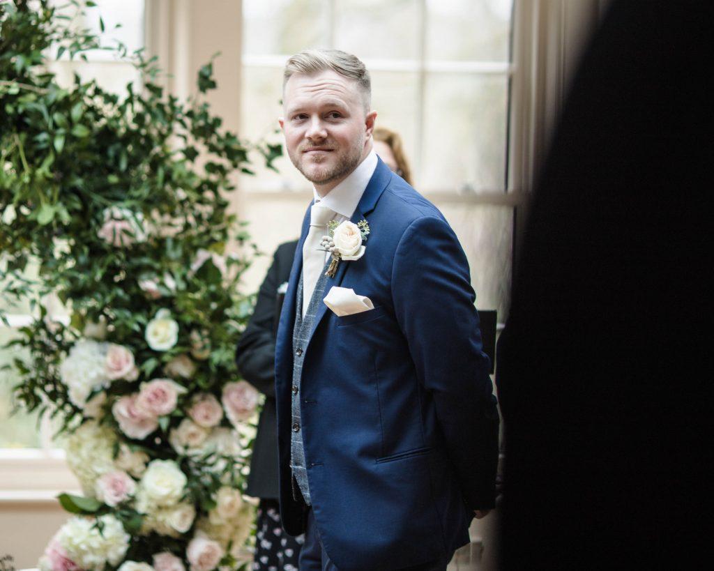 the groom as his bride walks down the aisle, creative wedding photography.