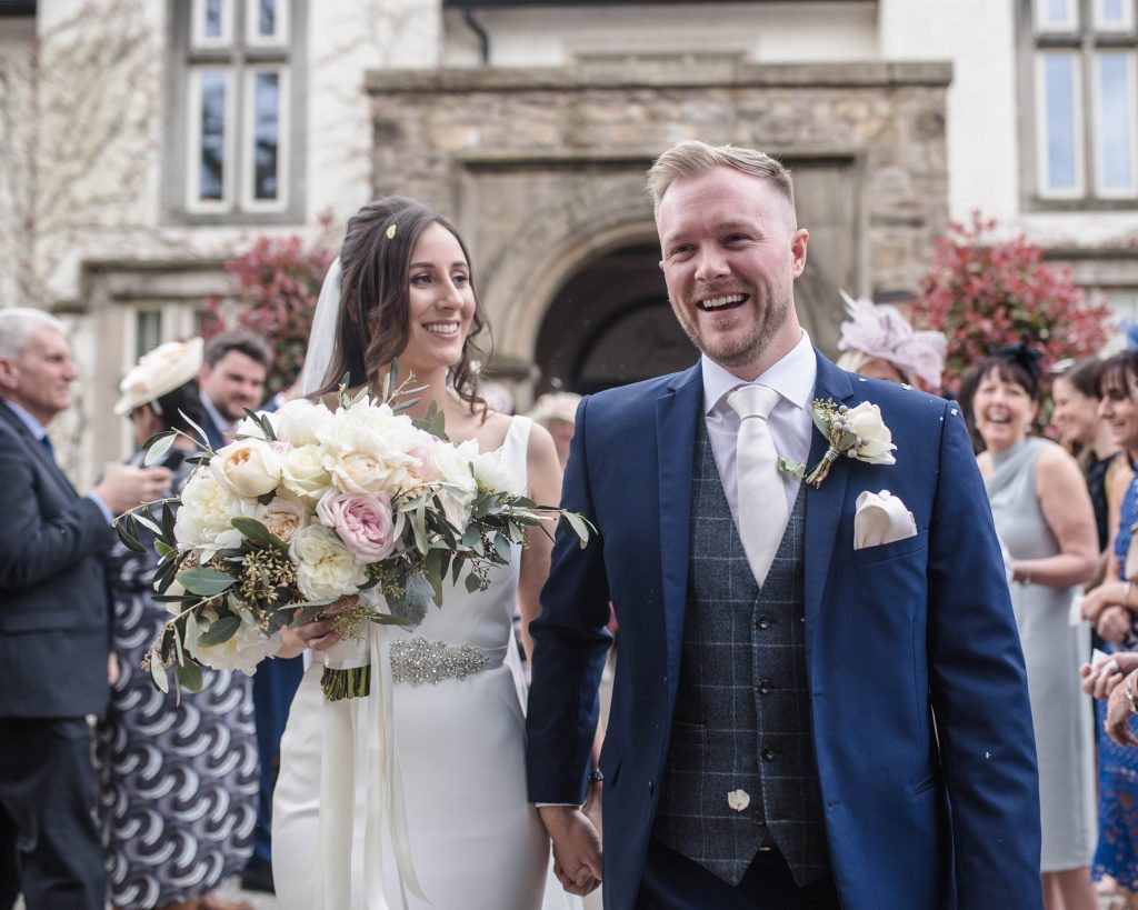 smiling bride and groom after the confetti. Mitton hall in the Ribble Valley.