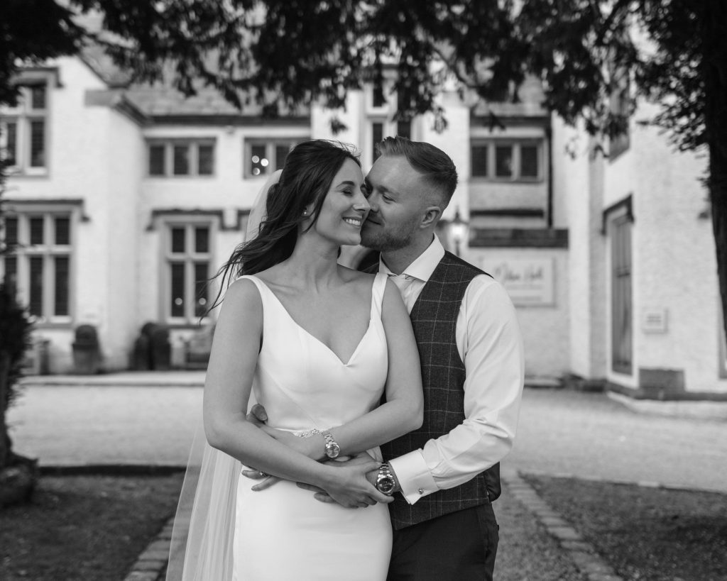 Black and white photograph of the bride and groom outside of mutton hall, wedding photographer Lancashire.Mitton hall in the Ribble Valley.