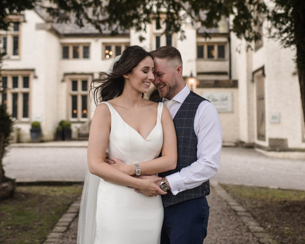 Just married couple cuddling outside of Mitton hall in the Ribble Valley.