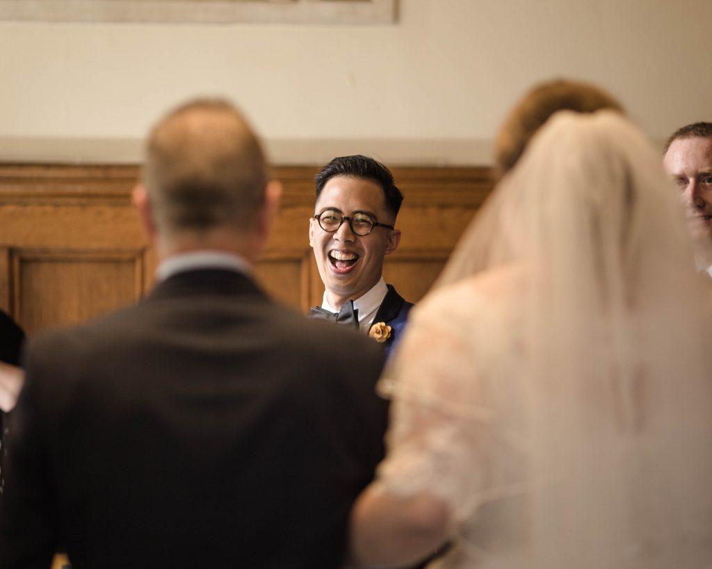 The groom as the bride walks down the aisle, documentary wedding photography.