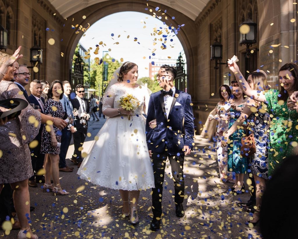 The bride and groom walking through confetti, creative wedding photography.