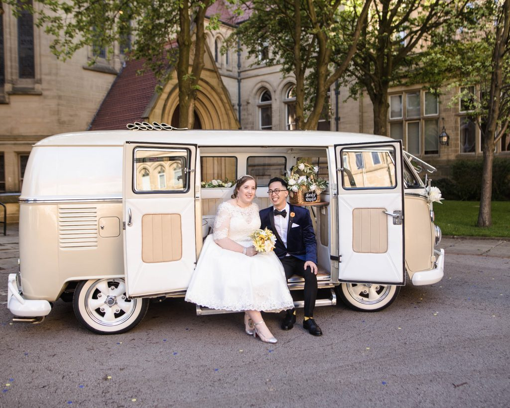 The bride and groom sat in a camper van, documentary wedding photography.