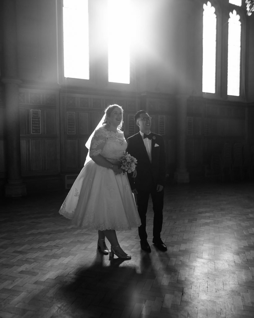 Black and white photograph of the bride and groom inside of the university of Manchester.