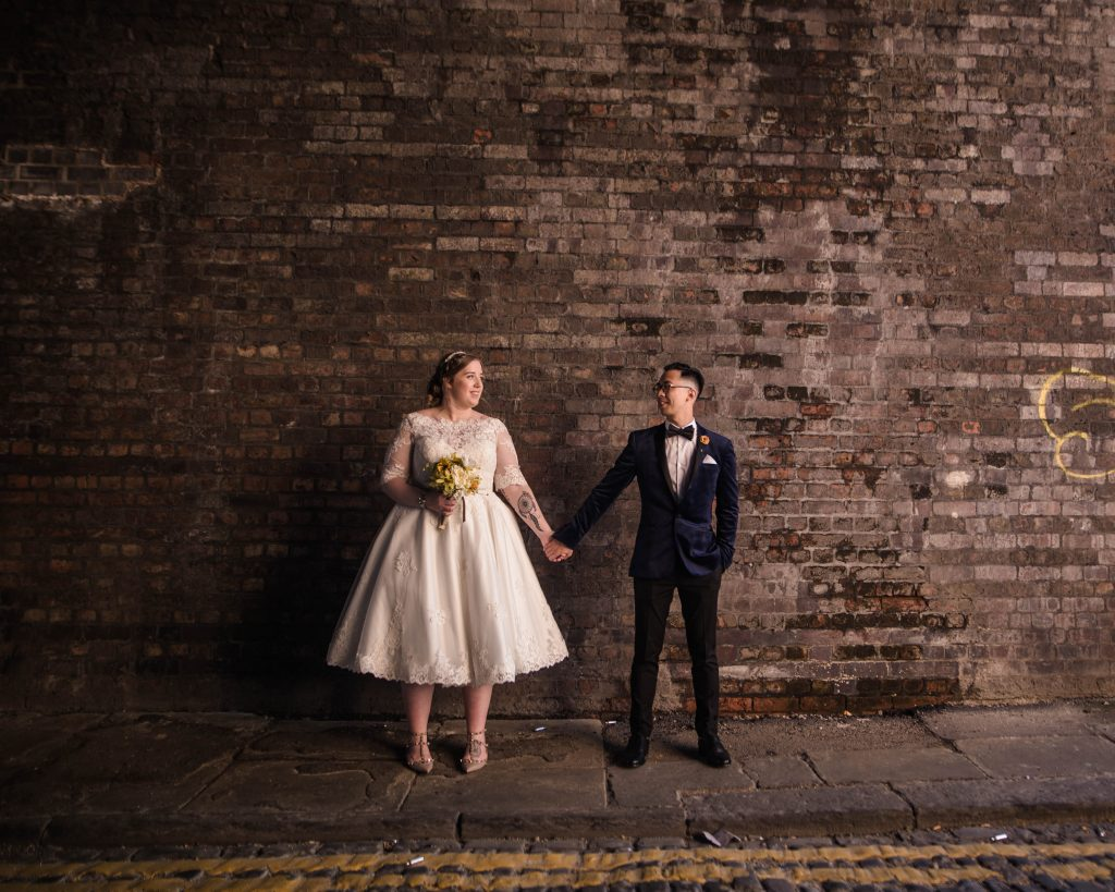 The bride and groom stood infant of a red brick wall. creative wedding photography.