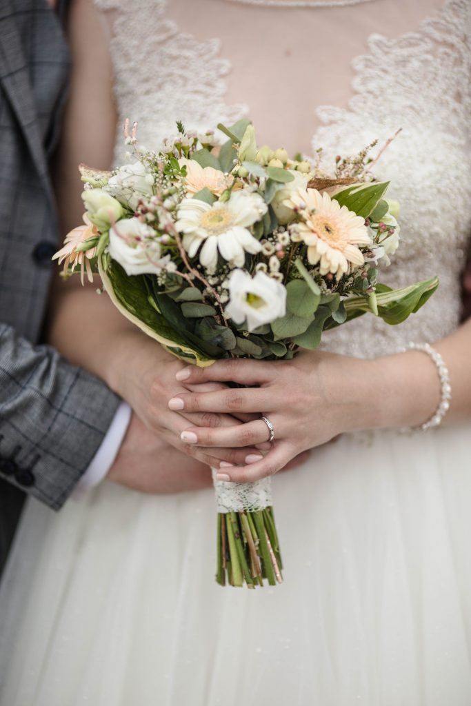 The bride and groom holding the bouquet, colourful wedding photography, lancashire wedding.
