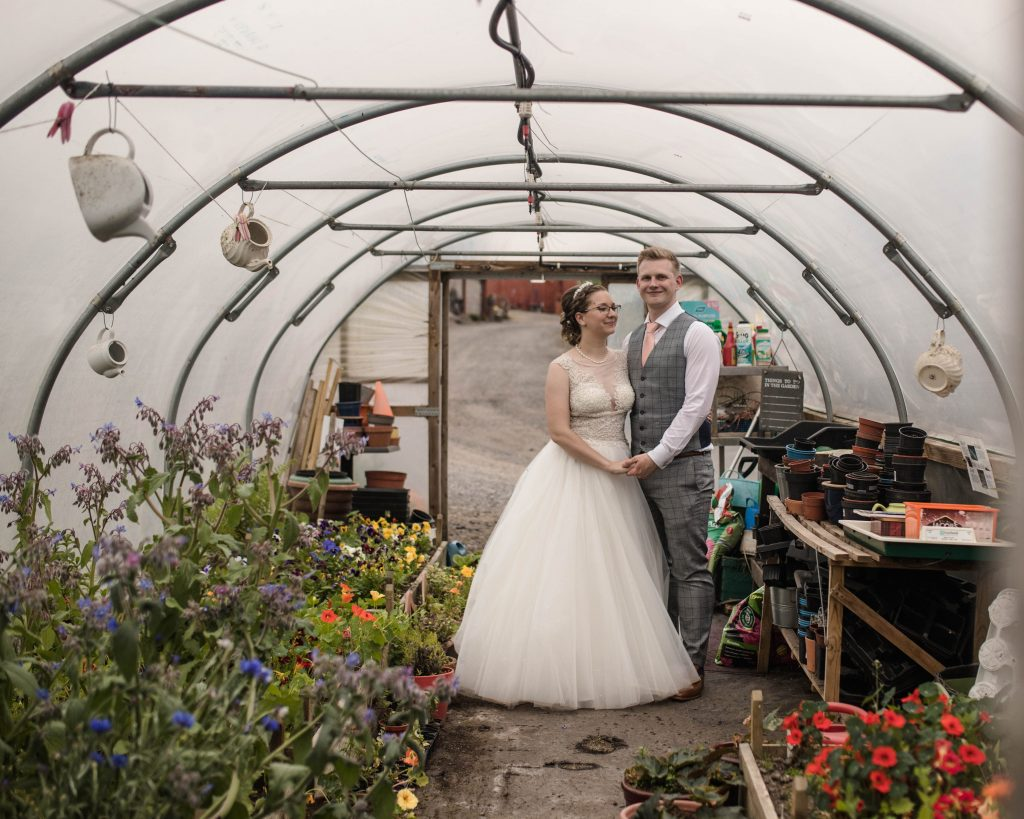 the bride and groom in the flower greenhouse at the wellbeing farm, creative wedding photography in lancashire.