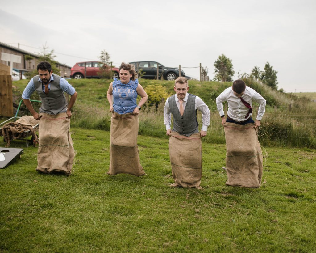 the groom joining in on the sack race, creative wedding photography.