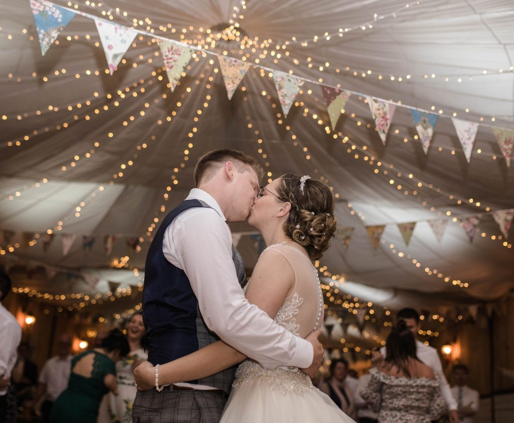 The bride and groom kissing during the first dance, documentary wedding photography.