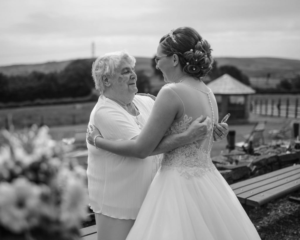 Black and white photograph of the bride hugging her grandma, documentary wedding photography in lancashire.