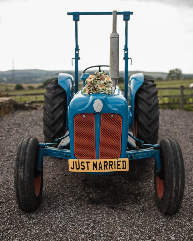 the bride flower bouquet on the tractor at the wellbeing farm in lancashire, colourful wedding photography.