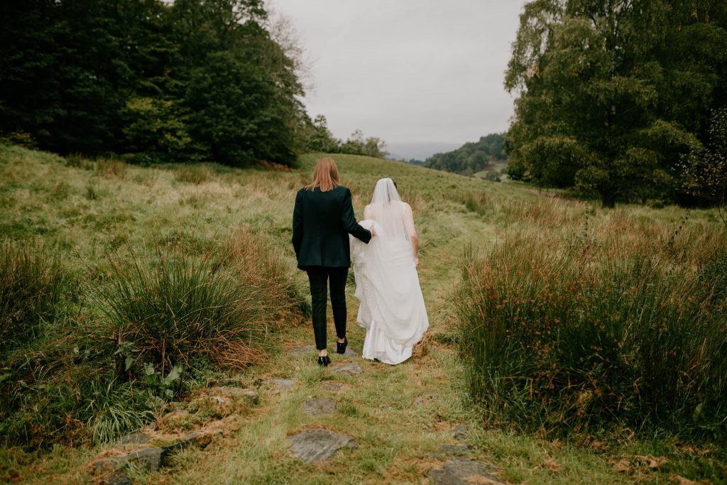 two brides walking through a field, Lake District wedding